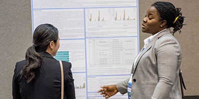 Two attendees talking in front of a poster presentation